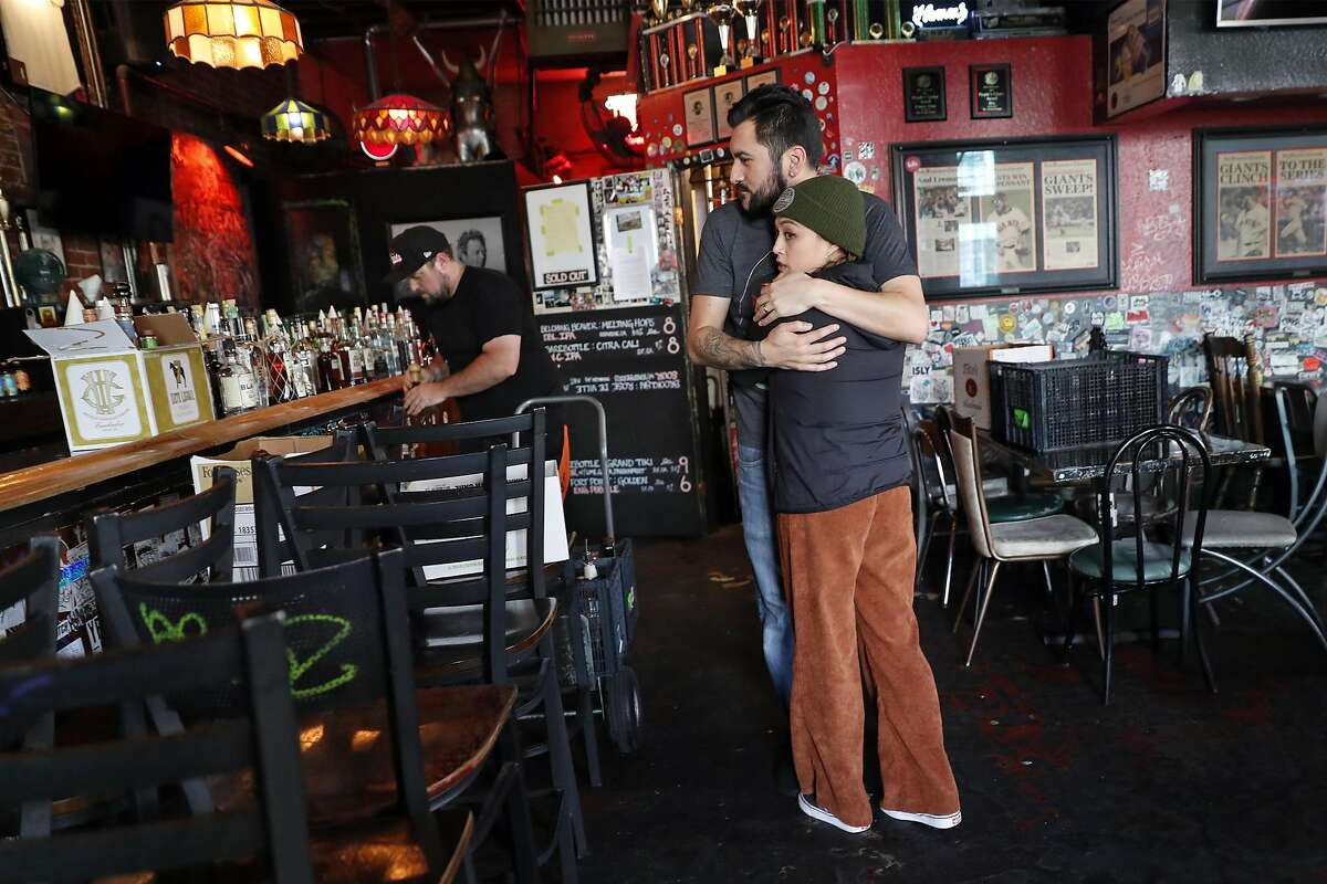 Tempest owner Justin Trujillo hugs friend, Nikki Nutterfield, after California Governor Gavin Newsom called for all bars closed due to coronavirus in San Francisco, Calif., on Sunday, March 15, 2020.