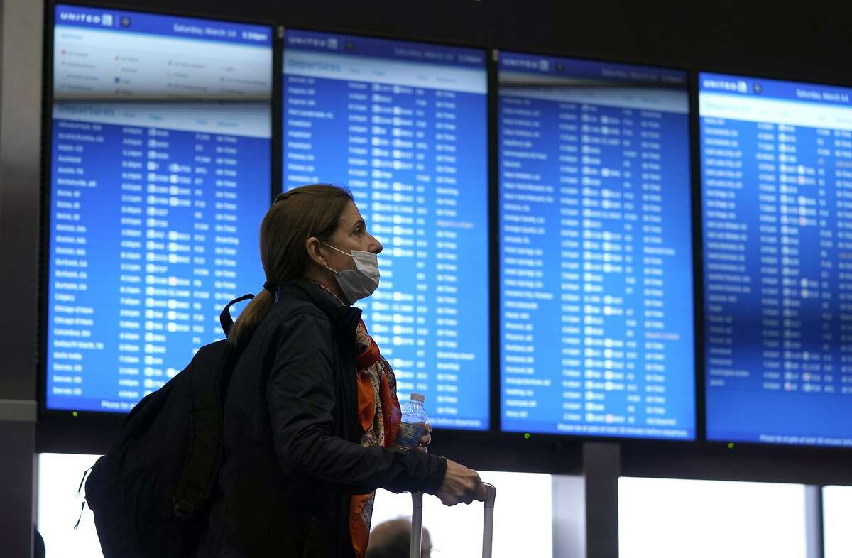 An airline passenger passes by a flight information board at San Francisco International Airport Saturday, March 14, 2020, in San Francisco.  (AP Photo/David J. Phillip)