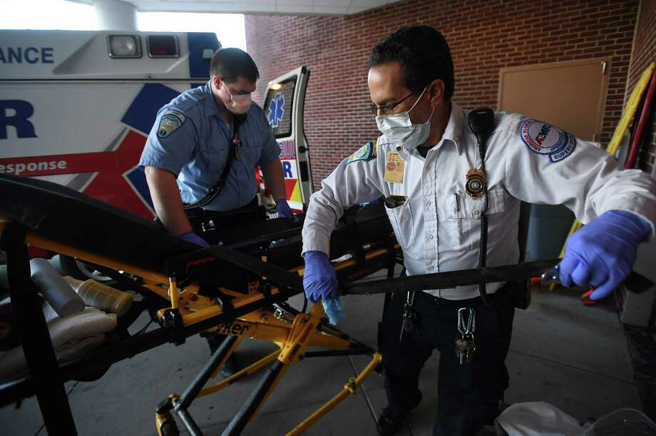 EMT Aiden Vrlik, left, and Operations Supervisor Robert Calzone clean and disinfect a stretcher during the decontamination of an AMR ambulance at Bridgeport Hospital in Bridgeport, Conn. on Sunday, March 15, 2020. Decontaminations have been undertaken for the last two weeks when patients exhibit potential coronavirus symptoms. Photo: Brian A. Pounds, Hearst Connecticut Media / Connecticut Post