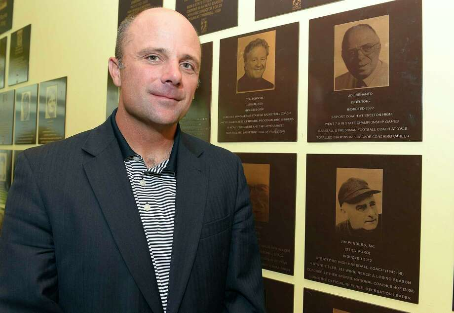 UConn baseball coach Jim Penders is photographed on June 7, 2018, in front of plaques depicting family members inducted into the Fairfield County Sports Hall of Fame during the inaugural UConn Huskies Coaches Road Show visit to the campus of UConn Stamford. Photo: Matthew Brown / Hearst Connecticut Media / Stamford Advocate