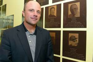 UConn baseball coach Jim Penders is photographed on June 7, 2018, in front of plaques depicting family members inducted into the Fairfield County Sports Hall of Fame during the inaugural UConn Huskies Coaches Road Show visit to the campus of UConn Stamford.