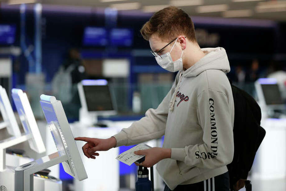 New York University student Hector Medrano, of Los Angeles, checks in for his flight using a touchscreen Saturday, March 14, 2020, at JetBlue's terminal in John F. Kennedy International Airport in New York. Medrano is traveling home during the school's spring break, and opted to wear a face mask as he travels to protect himself. Photo: AP Photo/Kathy Willens
