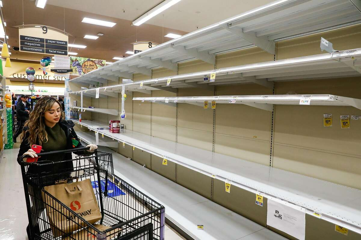 A woman walks past empty shelves at Safeway on 16th Street on Sunday, March 15, 2020 in San Francisco, California. The coronavirus has caused shoppers to stock up on various items like water and toilet paper.