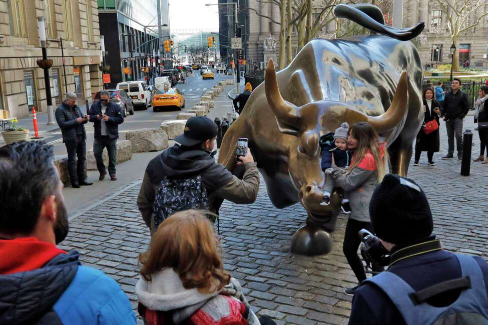 People pose for photos with the Charging Bull statue in New York's Financial District, Sunday, March 15, 2020. New York Gov. Andrew Cuomo. Cuomo said Saturday that more than 600 New Yorkers have been diagnosed with COVID-19, the disease caused by the virus. (AP Photo/Richard Drew)
