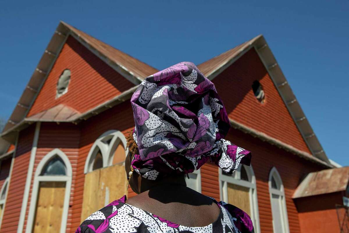 """Pastor Shetigho Agbuke, 67, stands outside at Redeemer's Praise Church in San Antonio, Texas, on March 6, 2020. Agbuke has ministered to those in need for the past nine years at the East Side building. """"Everything I did, I was always taking care of people,"""" says Agbuke of her life before becoming an ordained minister in 1994. """"I know that God called me to do this,"""" she went onto say. """"When I stepped into my calling everything fell into place. Once you take the calling- the help comes,"""" Agbuke says. """"Our time is so short... What you can do to make your corner of the world wonderful- do your part."""""""
