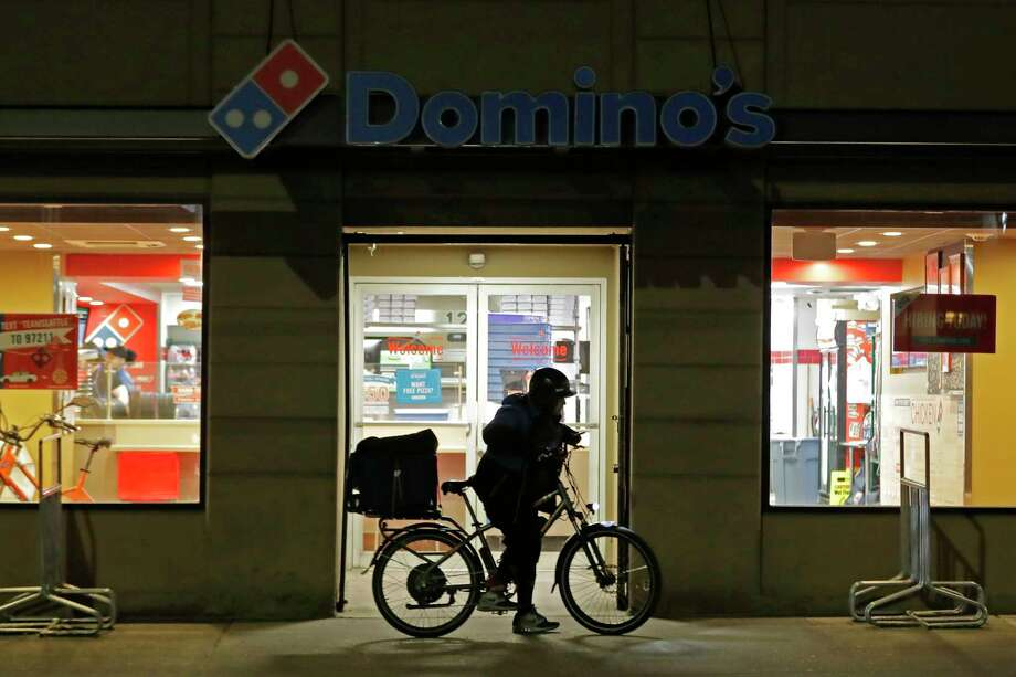 A delivery driver leaves a Domino's Pizza restaurant in downtown Seattle on a bike, Sunday, March 15, 2020. Washington Gov. Jay Inslee said Sunday night that he would order all bars, restaurants, entertainment and recreation facilities in the state to temporarily close to fight the spread of the COVID-19 coronavirus. Inslee said that restaurants could continue take-out and delivery services. Photo: Ted S. Warren, AP / Copyright 2020 The Associated Press. All rights reserved.