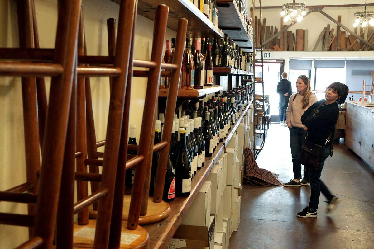 Joey Mazzera, right, and Reba Gray, left, shop wine at Ordinaire Wine Shop and Wine Bar that stopped bar service in Oakland, Calif., on Sunday, March 15, 2020, following an announcement by California Governor Gavin Newsom. The governor's announcement directs bars, wineries, nightclubs and breweries to close to curtail the spread of the Covid-19 virus, and stopped short of requiring restaurants to do so, but that they should cut seating capacity. Ordinaire it stopping bar service and keeping only retail service, asking customers to not touch the wine bottles, having employees handle the bottles for them.