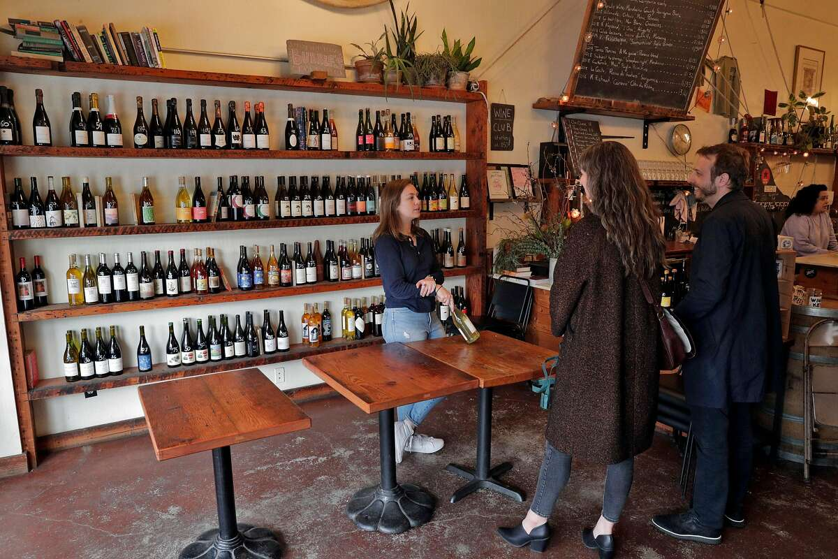 Marin Hood, center and JP Leimone, right, are helped by Claire Cerda as they shop for wine at Ordinaire Wine Shop and Wine Bar that stopped bar service in Oakland, Calif., on Sunday, March 15, 2020, following an announcement by California Governor Gavin Newsom. The governor's announcement directs bars, wineries, nightclubs and breweries to close to curtail the spread of the Covid-19 virus, and stopped short of requiring restaurants to do so, but that they should cut seating capacity. Ordinaire it stopping bar service and keeping only retail service, asking customers to not touch the wine bottles, having employees handle the bottles for them.
