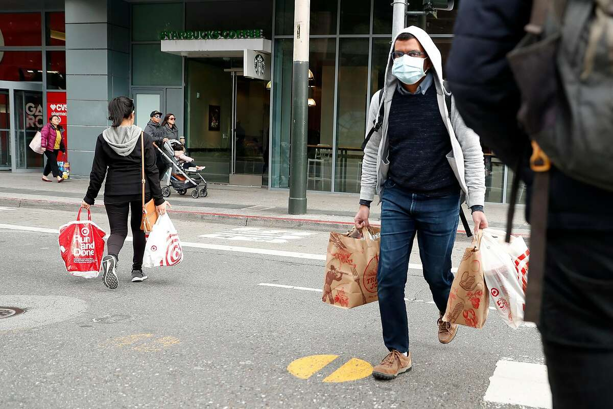 Shoppers cross Mission Street in San Francisco, Calif., on Sunday, March 15, 2020.