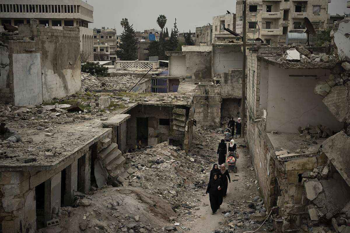 In this Thursday, March 12, 2020 photo, women walk in a neighborhood heavily damaged by airstrikes in Idlib, Syria. Idlib city is the last urban area still under opposition control in Syria, located in a shrinking rebel enclave in the northwestern province of the same name. Syria's civil war, which entered its 10th year Monday, March 15, 2020, has shrunk in geographical scope -- focusing on this corner of the country -- but the misery wreaked by the conflict has not diminished. (AP Photo/Felipe Dana)