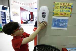 Emiliano Arango, 7, uses the hand sanitizer at the Heights Boys and Girls Club, in Houston,Thursday, March 12, 2020. State officials are calling for schools to reopen on time in August, despite pleas from teachers and others that the health risks are too high.