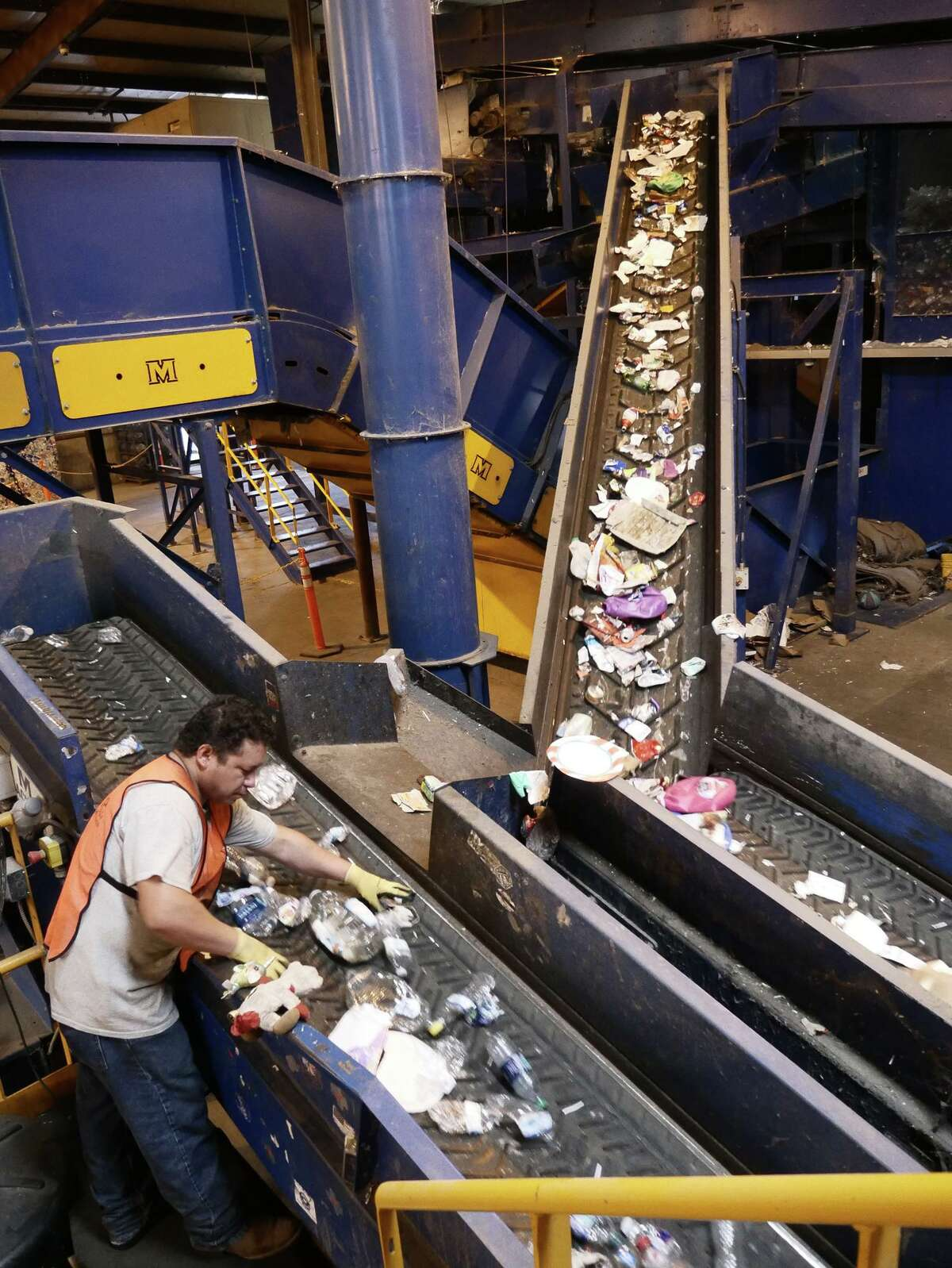 An employee of the Laredo Solid Waste Department manually separates the recyclable material that is deposited at the recycling center.