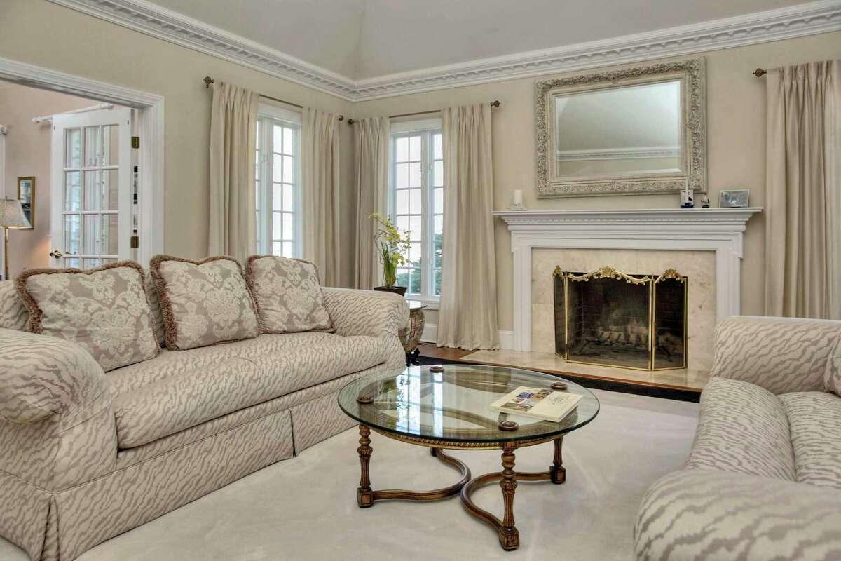 The formal living room has decorative millwork and a marble fireplace.