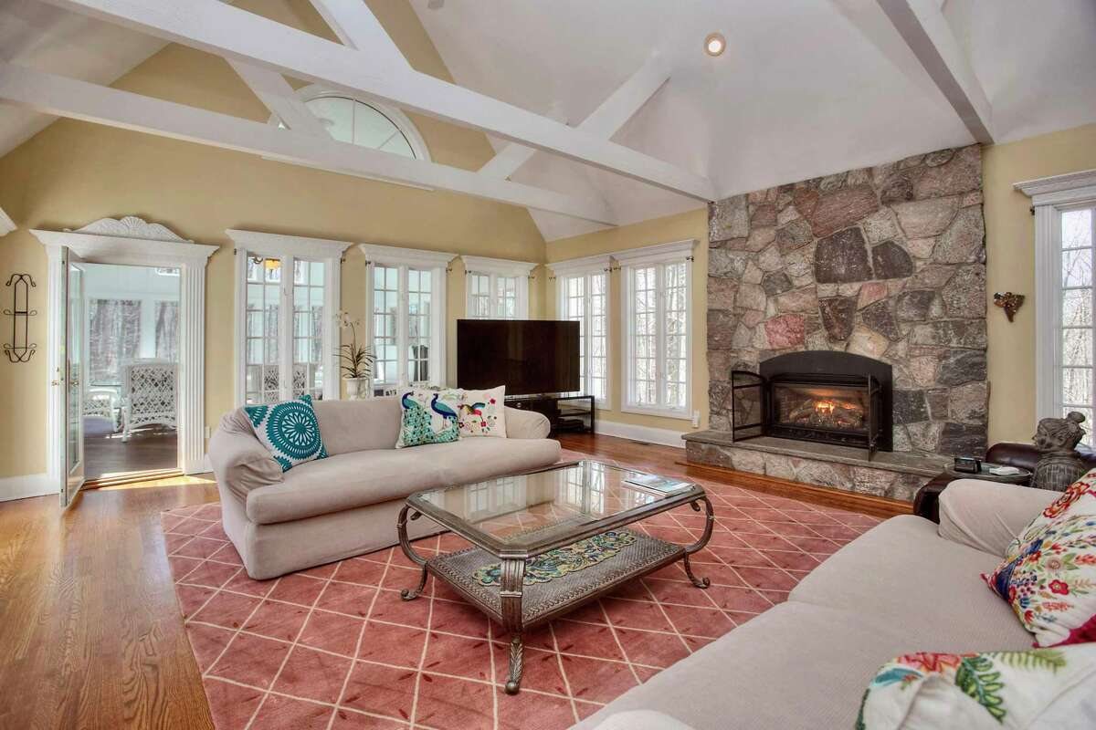 In the family room there is a cathedral ceiling with trestle beams, a floor-to-ceiling gas log stone fireplace, and a door to a large sun room.