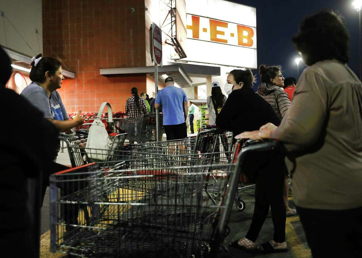 Shoppers, including Janis Campos with her mask, line up early to be the first ones to get in at Olmos Park H-E-B, on Monday, March 16, 2020.