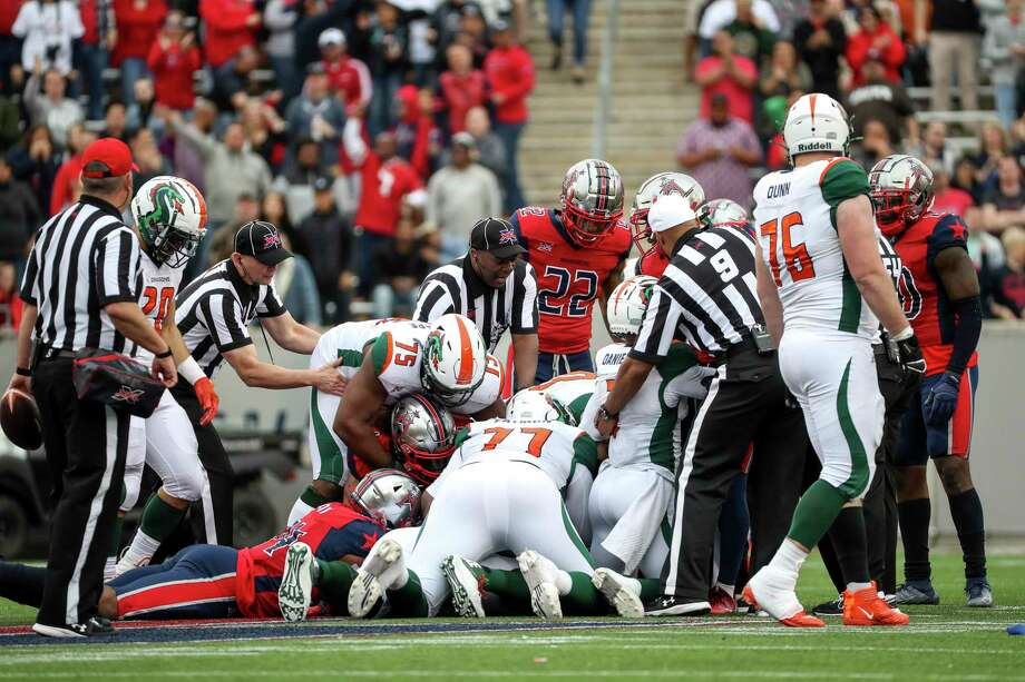 Houston Roughnecks and Seattle Dragons players go after a fumble during the fourth quarter of an XFL game on Saturday, March 7, 2020, at TDECU Stadium in Houston. The XFL has confirmed that an unidentified Seattle Dragons player tested positive for novel coronavirus. On March 12, 2020, the league suspended its 2020 season. Photo: Jon Shapley / Staff Photographer / © 2020 Houston Chronicle
