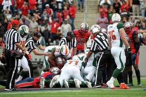 Houston Roughnecks and Seattle Dragons players go after a fumble during the fourth quarter of an XFL game on Saturday, March 7, 2020, at TDECU Stadium in Houston. The XFL has confirmed that an unidentified Seattle Dragons player tested positive for novel coronavirus. On March 12, 2020, the league suspended its 2020 season.