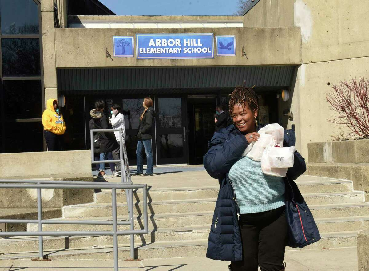 Gloria Myers of Albany picks up some free meals for her children at Arbor Hill Elementary School which is closed to deal with the coronavirus on Monday, March 16, 2020 in Albany, N.Y. Lunch for the current day and breakfast for the following day will be available to district students at various locations each weekday through Friday, March 27. (Lori Van Buren/Times Union)