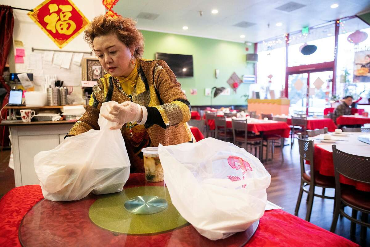 Nina Wei prepares pickup orders at Hubei Restaurant on Saturday, March 14, 2020, in Millbrae, Calif. When restaurant owner Nina Wei opened it just under three years ago, she envisioned a meeting place for people passionate about the culture of the Hubei Province in the central part of China, with a unique cuisine that�s partly spicy and partly not, full of freshwater fish and specialty vegetables. It was doing well until January, when due to its unfortunate name � Wuhan, the city where the coronavirus outbreak was first detected, is in Hubei Province � the restaurant started receiving cancellations. Wei has laid off all but one staff member and serves the remaining customers herself.