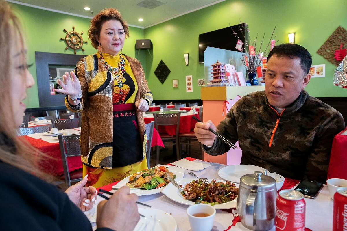 Nina Wei attends to customers at Hubei Restaurant on Saturday, March 14, 2020, in Millbrae, Calif. When restaurant owner Nina Wei opened it just under three years ago, she envisioned a meeting place for people passionate about the culture of the Hubei Province in the central part of China, with a unique cuisine that�s partly spicy and partly not, full of freshwater fish and specialty vegetables. It was doing well until January, when due to its unfortunate name � Wuhan, the city where the coronavirus outbreak was first detected, is in Hubei Province � the restaurant started receiving cancellations. Wei has laid off all but one staff member and serves the remaining customers herself.