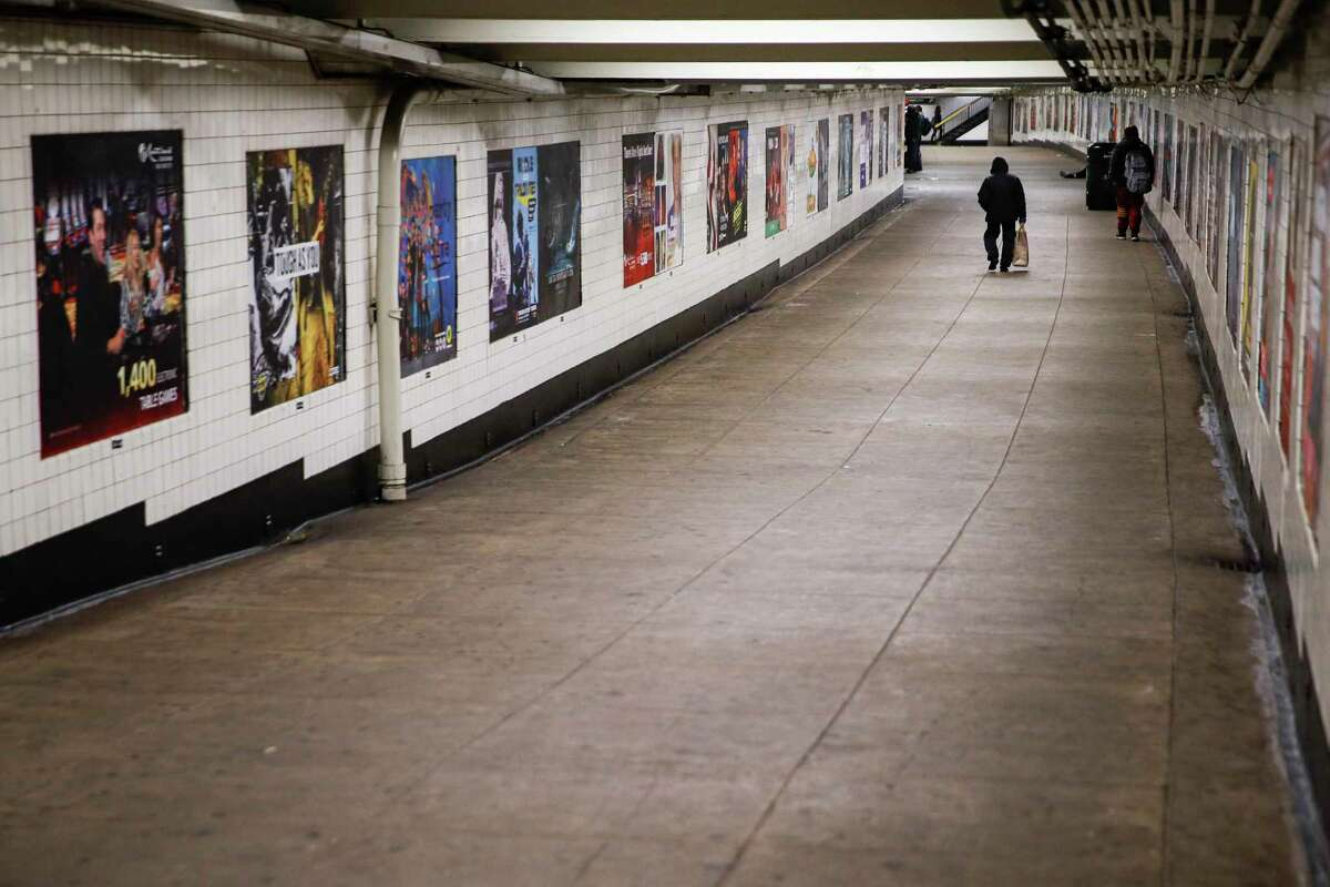 A subway customer walks through an empty underground passage in the Brooklyn borough of New York, Monday, March 16, 2020. New York leaders took a series of unprecedented steps Sunday to slow the spread of the coronavirus, including canceling schools and extinguishing most nightlife in New York City. According to the World Health Organization, most people recover in about two to six weeks, depending on the severity of the illness.