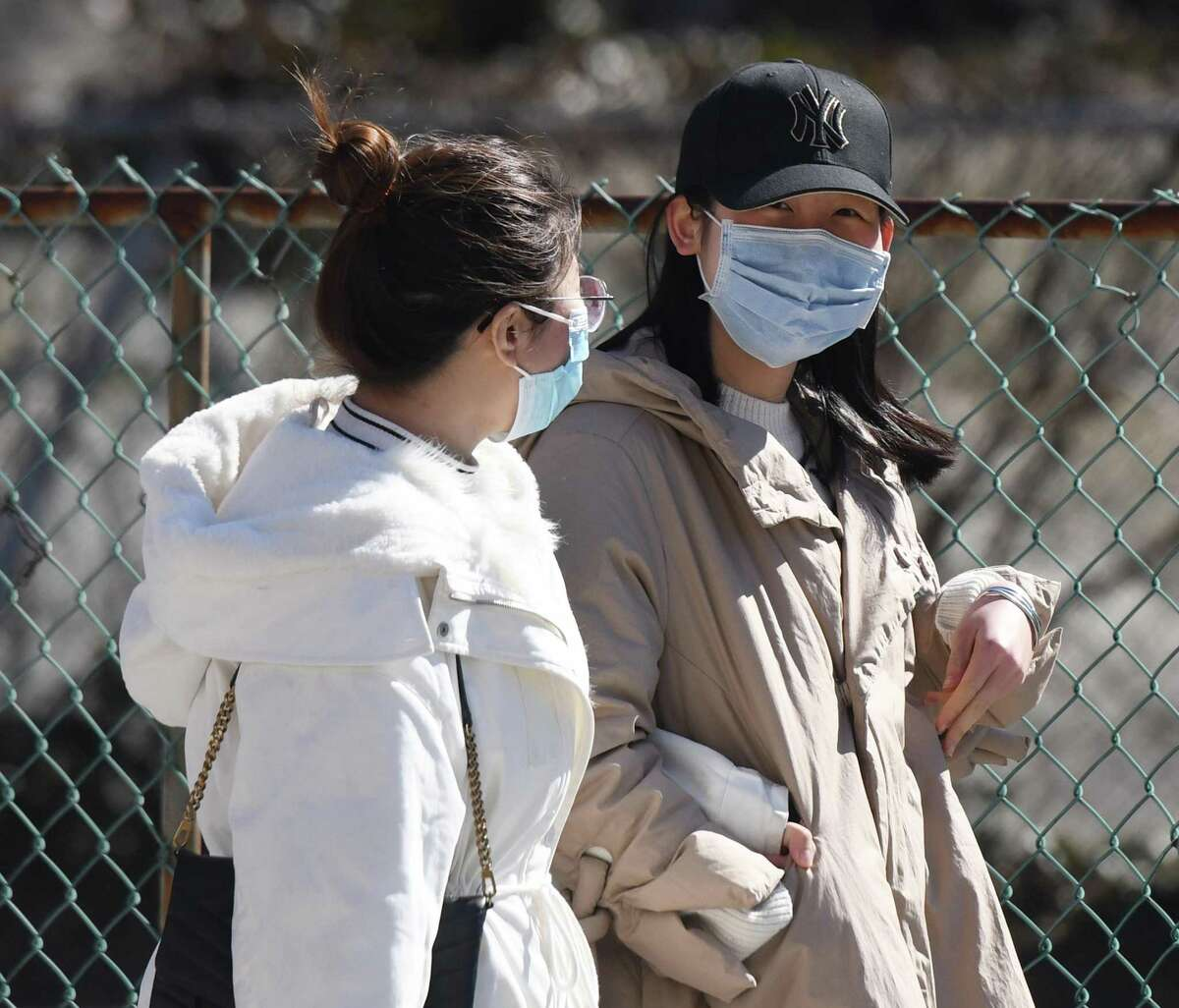 Two women wear masks to protect against the coronavirus as they walk down the street in Stamford on Sunday.