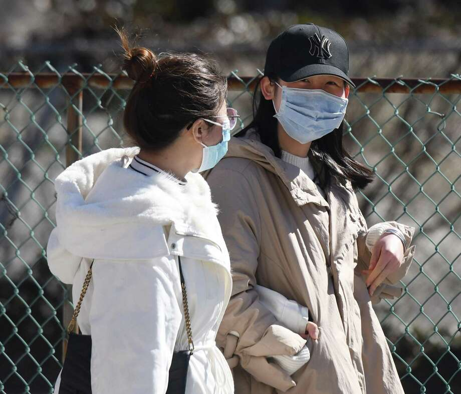 Two women wear masks to protect against the coronavirus as they walk down the street in Stamford on Sunday. Photo: Tyler Sizemore / Hearst Connecticut Media / Greenwich Time