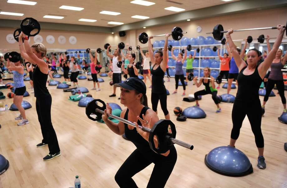 File photo from 2013 shows members of a Life Time gym in the San Antonio area lift weights during a high intensity interval training (HIIT) session. Photo: Robin Jerstad, Freelance