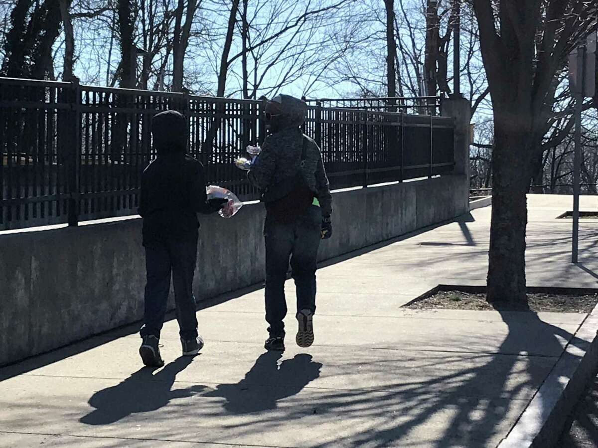 A parent and child leave Beecher School with grab-and-go breakfast and lunch on March 16, 2020.