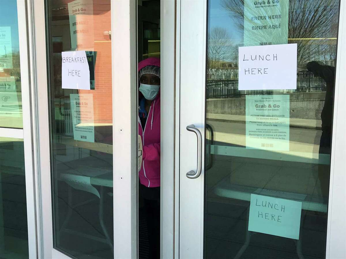 Dawn Rogers, lead cook at Beecher School in New Haven, cracks open the door during a school shutdown on March 16, 2020. Rogers and other food service workers are disseminating grab-and-go meals for students.