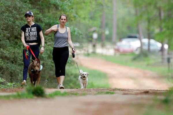 Women walk their dogs through William Goodrich Jones State Forest, Saturday, March 14, 2020, in Conroe.