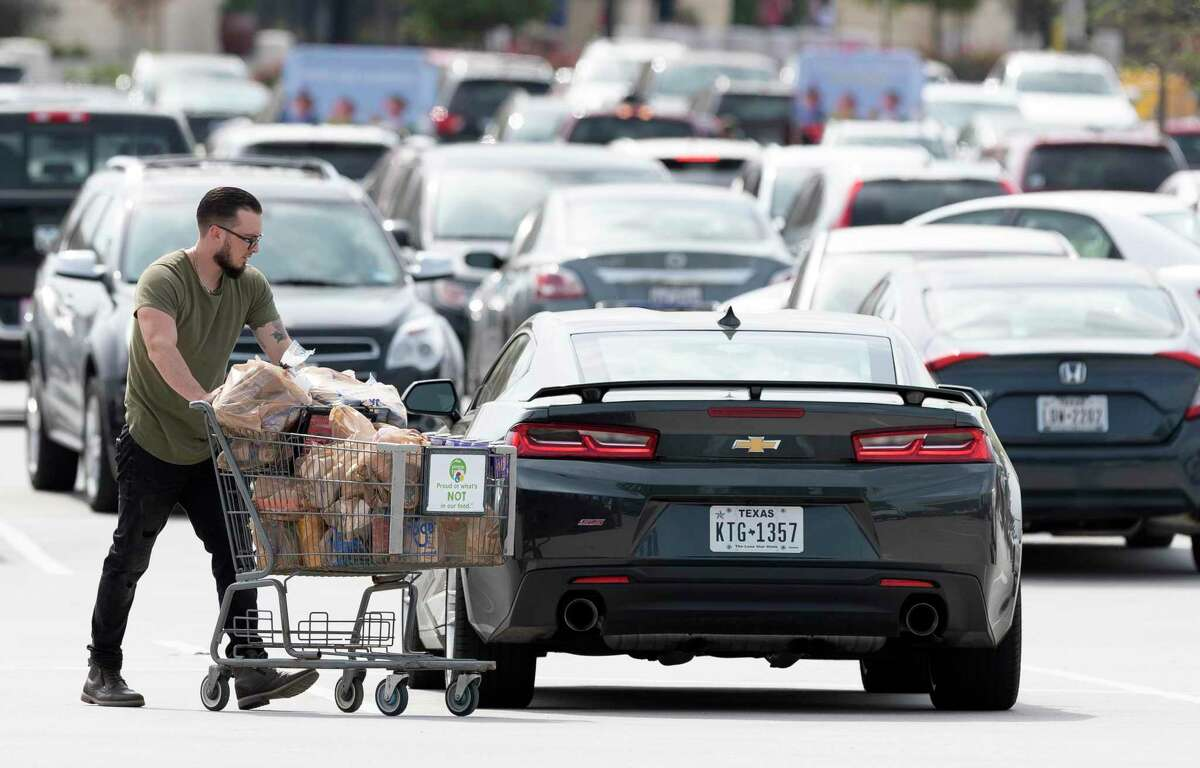 Ryan Spencer wheels groceries to his car at Kroger along South Loop 336, Friday, March 13, 2020, in Conroe. Spencer said the store was either out or low on several items including milk and meat.