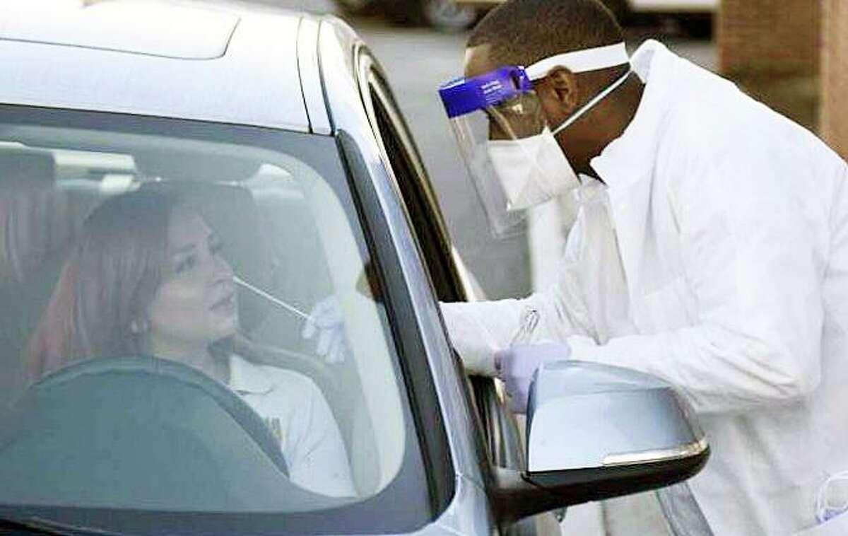Phlebotomist Warren Dawkins demonstrates drive-thru testing for coronavirus at Murphy Medical Associates in Greenwich, Conn. Monday, March 9, 2020