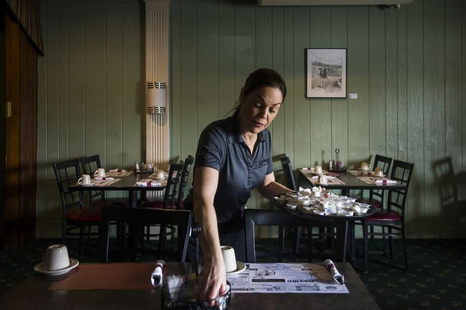 Dana Cox, a server at Shirlene's Cuisine, collects packets of margarine to refrigerate them Monday, March 16, 2020 during the last day the restaurant will be open to dine-in customers after Gov. Gretchen Whitmer issued a sweeping order banning dine-in customers at restaurants and closing all bars, movie theaters, gyms and other sports facilities to curb the spread of the coronavirus. (Katy Kildee/kkildee@mdn.net) Photo: (Katy Kildee/kkildee@mdn.net)