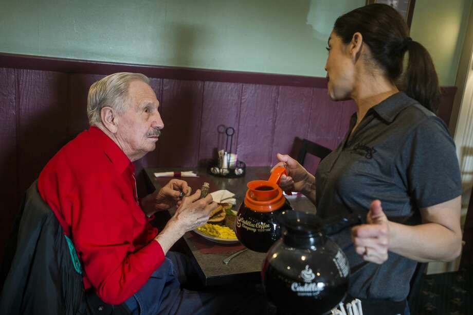 Dana Cox, a server at Shirlene's Cuisine, chats with customer Joseph Benes Monday, March 16, 2020 during the last day the restaurant will be open to dine-in customers after Gov. Gretchen Whitmer issued a sweeping order banning dine-in customers at restaurants and closing all bars, movie theaters, gyms and other sports facilities to curb the spread of the coronavirus. (Katy Kildee/kkildee@mdn.net) Photo: (Katy Kildee/kkildee@mdn.net)