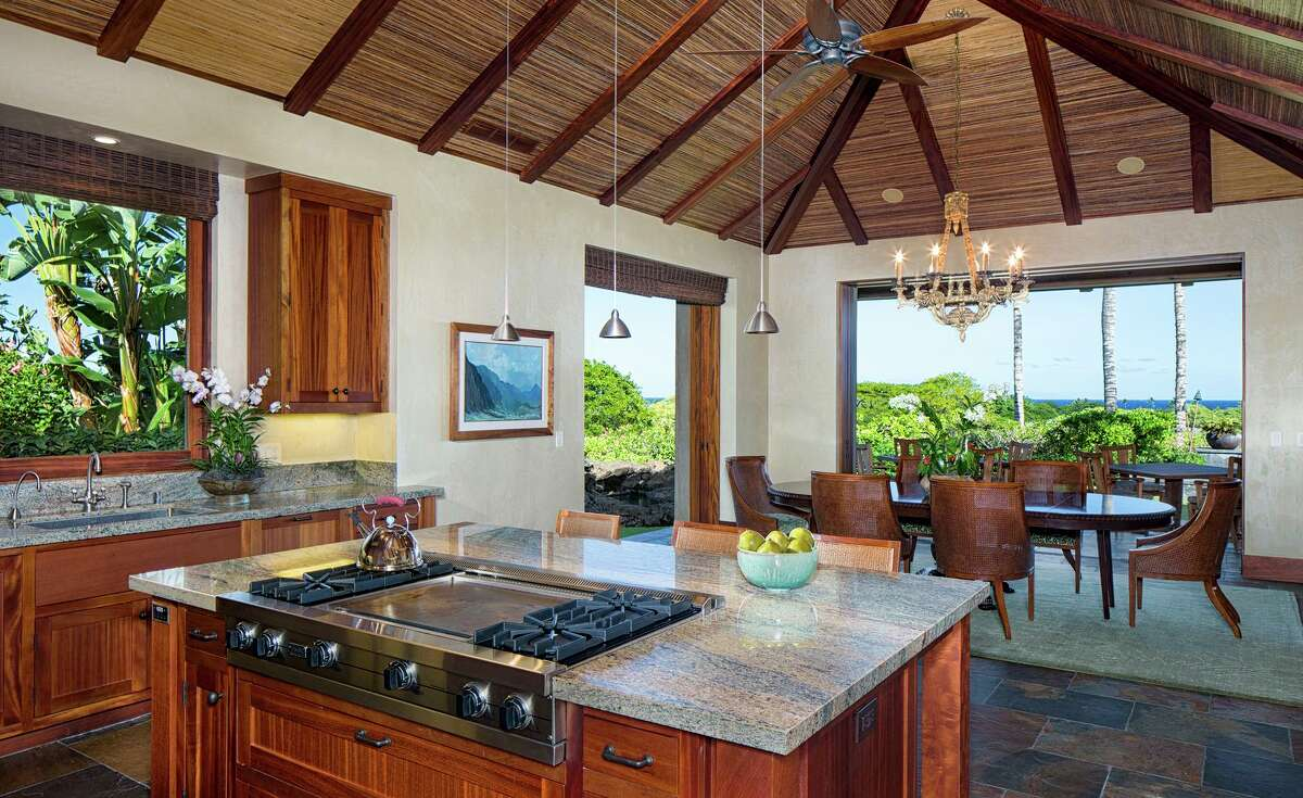 Slate flooring lines an open kitchen revolving around a stone-topped island with a built-in cooktop.