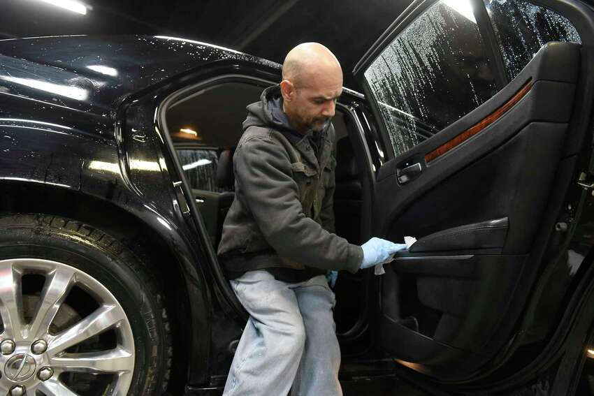 Premiere Transportation employee Jose Barreto cleans one of the cars at Premiere Transportation on Monday, March 16, 2020 in Albany, N.Y. The company is taking extra precautions because of the coronavirus. (Lori Van Buren/Times Union)