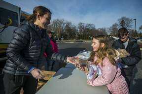 Volunteer Kayla Contardi, left, hands a school lunch to Brooklyn Deisler, 9, Monday, March 16, 2020 at the Greater Midland Community Center. Several Midland Public School school buildings, as well as other designated pick-up locations, will be open for meal pick-up on Monday, Wednesday, and Friday until April 3. (Katy Kildee/kkildee@mdn.net)