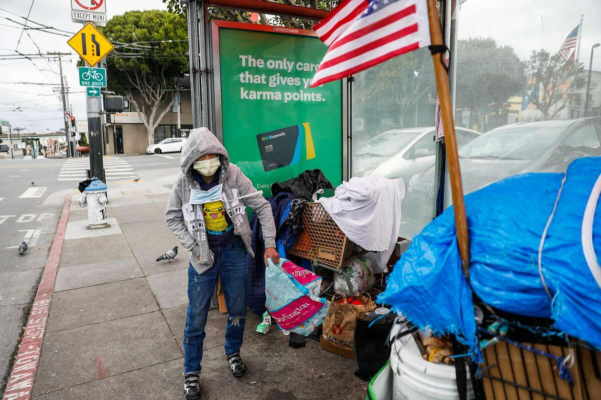 A homeless woman who wished to remain anonymous wears a mask as she prepares her belongings on Sunday, March 15, 2020 in San Francisco, California.