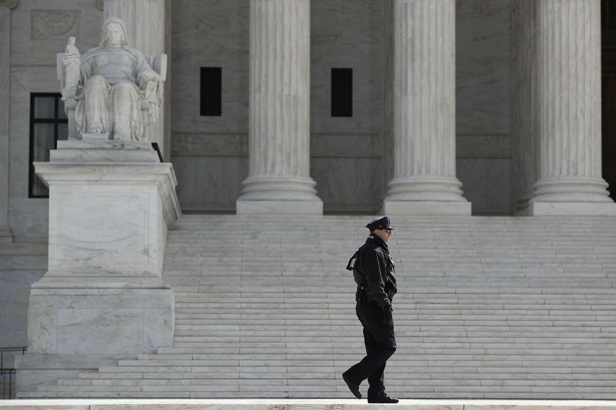 A police officer walks outside the Supreme Court in Washington, Monday, March 16, 2020. The Supreme Court announced Monday that it is postponing arguments for late March and early April because of the coronavirus, including fights over subpoenas for President Donald Trump's financial records. (AP Photo/Patrick Semansky)