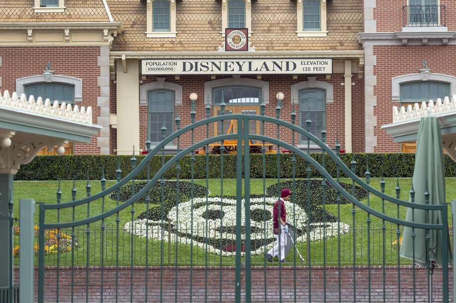 An employee cleans the grounds behind the closed gates of Disneyland Park on the first day of the closure of Disneyland and Disney California Adventure theme parks as fear of the spread of coronavirus continue, in Anaheim on March 14, 2020. Photo: DAVID MCNEW/AFP Via Getty Images