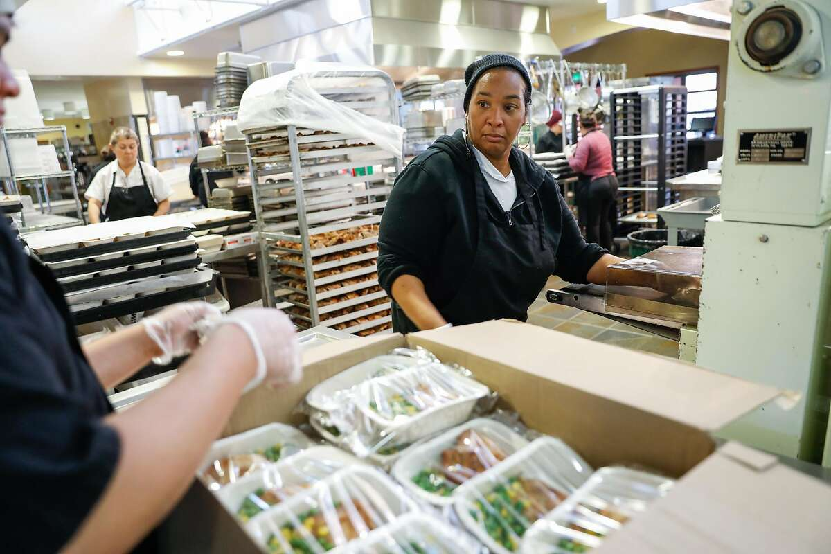 La Shell Newman helps organize freshly sealed food at King Middle School on Monday, March 16, 2020 in Berkeley, California. Public Schools have been closed because of the coronavirus but many students who are normally fed during school will have the ability to pick up bagged meals.