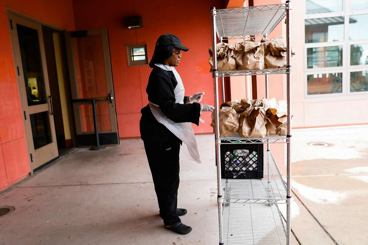 Catherine Alexander organizes bagged food outside King Middle School for pick up on Monday, March 16, 2020 in Berkeley, California. Public Schools have been closed because of the coronavirus but many students who are normally fed during school will have the ability to pick up bagged meals.