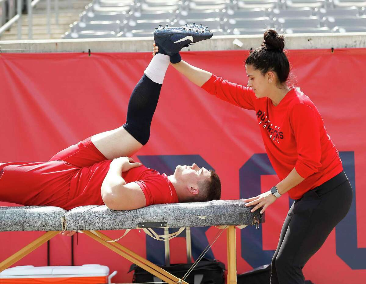 Mariana Del Pilar, 23, assistant strength and conditioning coach for the XFL Roughnecks stretches out Colton Taylor at TDECU stadium during workouts, in Houston,Wednesday, March 11, 2020.