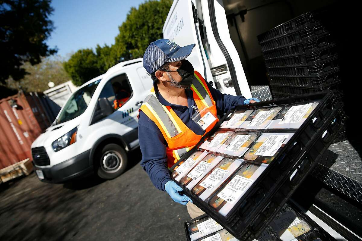 Santos Cetina, Meals on Wheels driver, places meals for delivery into a van at Meals on Wheels on Thursday, March 12, 2020 in San Francisco, Calif.
