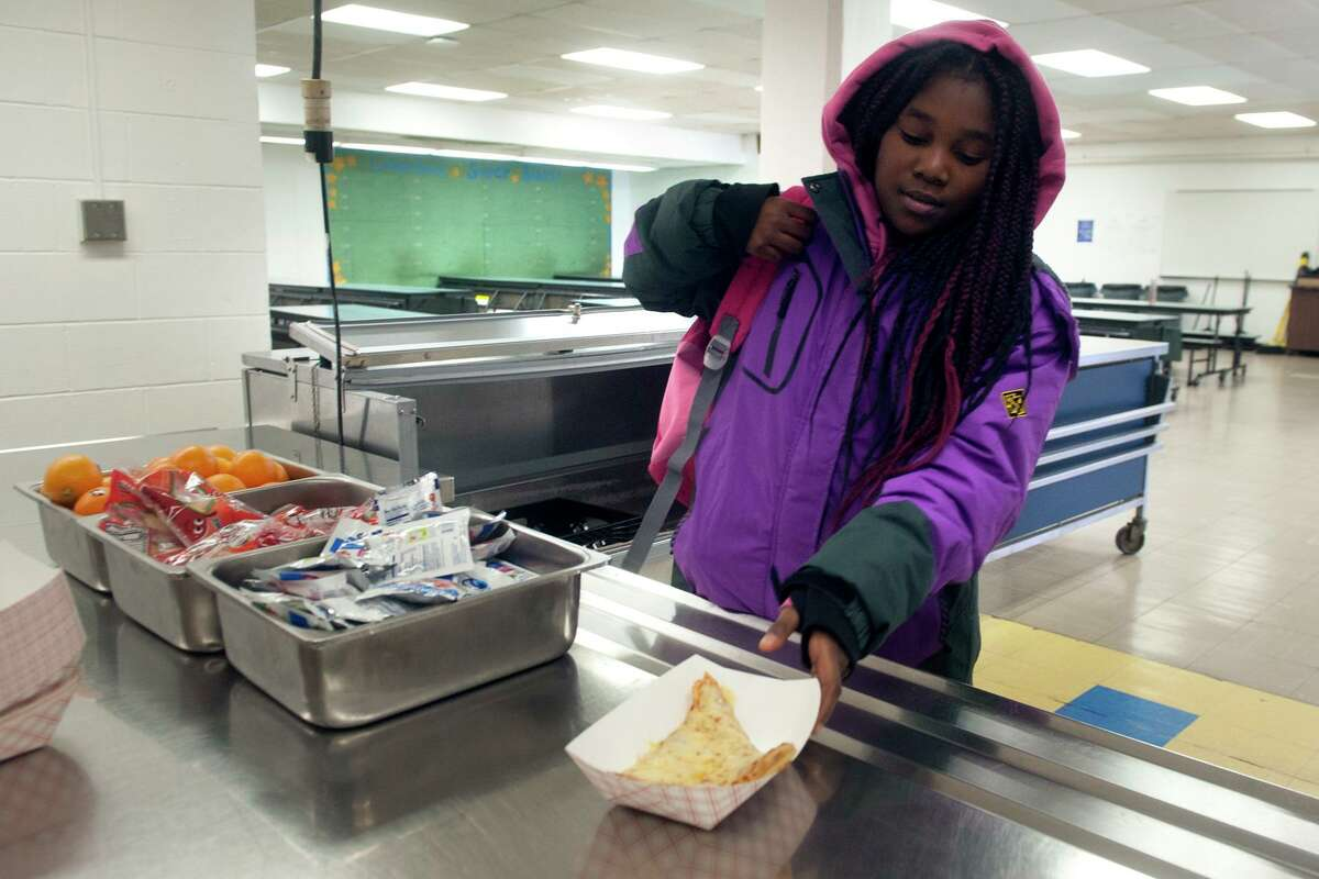 Fifth grader Jeriyah Smith picks up a slice of pizza during a lunchtime visit to the cafeteria at Columbus School, in Bridgeport, Conn. March 16, 2020. Following the closing of schools last week, Bridgeport began serving breakfast and lunch meals to go for city students on Monday.
