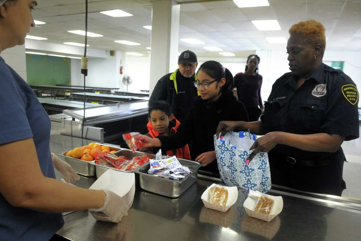 Security guard Karen Montabo, right, helps students Mathew and Brisa and Mendez as they make for a lunchtime visit to the cafeteria at Columbus School, in Bridgeport, Conn. March 16, 2020. Following the closing of schools last week, Bridgeport began serving breakfast and lunch meals to go for city students on Monday.