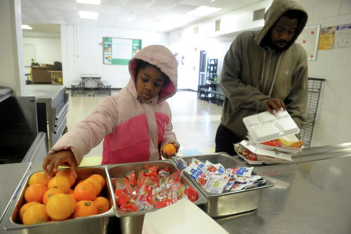 Third grader Nevaeh Ludd picks up a couple of oranges during a lunchtime visit to the cafeteria at Columbus School, in Bridgeport, Conn. March 16, 2020. Following the closing of schools last week, Bridgeport began serving breakfast and lunch meals to go for city students on Monday. Ludd is accompanied here by her uncle, Tremaine Shepherd.