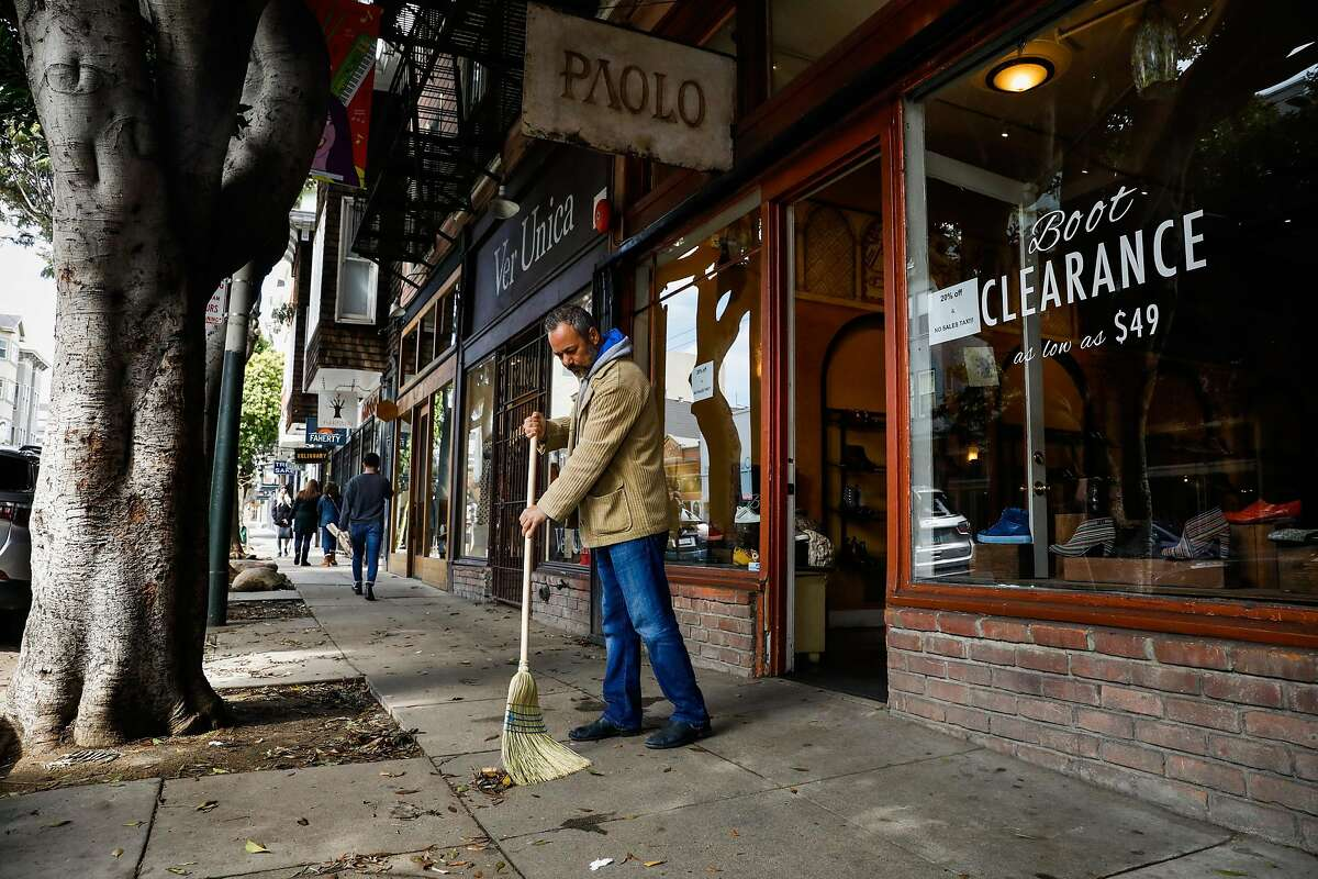 Chaari A., owner of Paolo sweeps outside his shop moments before Mayor London Breed announced that six Bay Area counties would lockdown non-essential services due to the coronavirus on Monday, March 16, 2020 in San Francisco, California