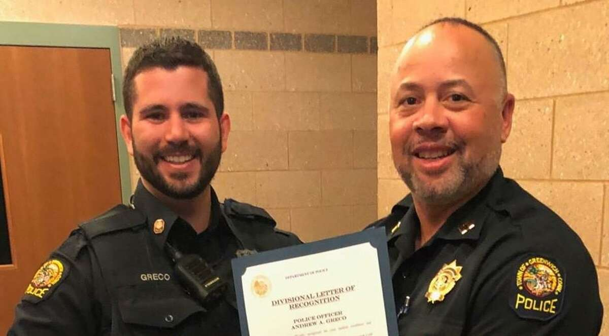 Officer Andrew Greco, left, was commended for carrying out CPR in a medical emergency. Police Capt. Kraig Gray presents him with a certificate.